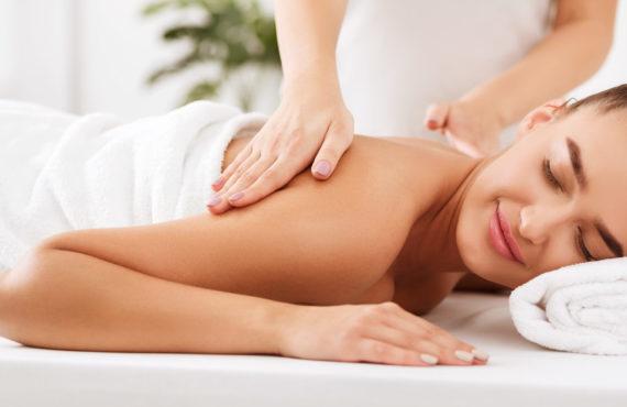 Spa treatment. Masseur doing shoulder massage on woman body, closeup